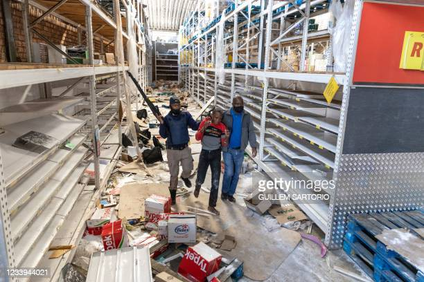 South African Police Services members arrest a looter at the Gold Spot Shopping Centre in Vosloorus, southeast of Johannesburg, on July 12, 2021. -...