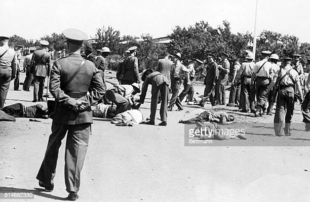 South African police walk by the bodies of demonstrators Over 50 people were killed when police opened fire on a crowd