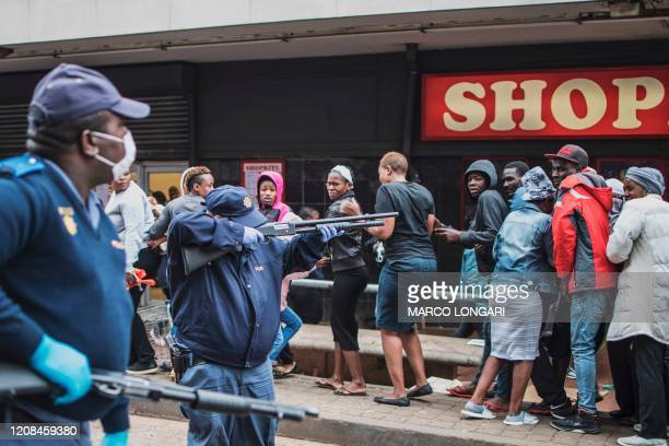 South African policeman points his pump rifle to disperse a crowd of shoppers in Yeoville Johannesburg on March 28 2020 while trying to enforce a...