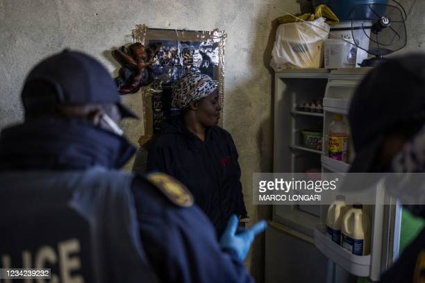 South African policemen question a woman about the content of her fridge at the Nguni Hostels in Vosloorus, on July 27, 2021 during a joint operation...
