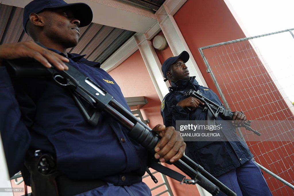 South African policemen stand guard as football fans wait to enter the O.R Tambo center and see the FIFA World Cup trophy after the unveiling on May 07, 2010 during the kick off of its South African tour in Kayelitsha on the outskirt of Cape Town, South Africa.
