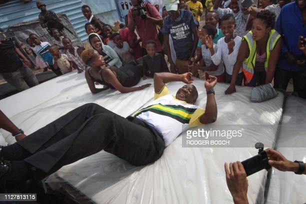 South African President and president of the ruling party the African National Congress Cyril Ramaphosa tests a bed that artisans make on the side of...