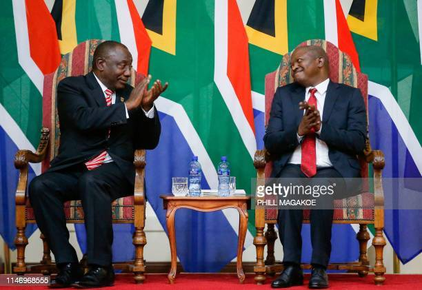 South African President Cyril Ramaphosa and his deputy David Mabuza react during a swearing in ceremony at Sefako Makgato Presidential Guesthouse on...