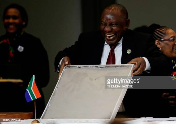 South African President Cyril Ramaphosa laughs as he shows his handprint in clay during the 10th BRICS summit on July 26, 2018 at the Sandton...