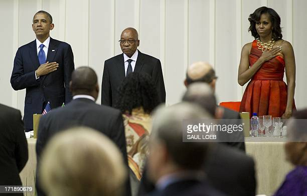South African President Jacob Zuma US President Barack Obama and First Lady Michelle Obama stand during the US national anthem during an official...