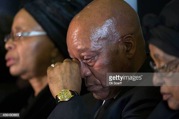 South African president Jacob Zuma wipes an eye as he sits with Graca Machel widow of Nelson Mandela and Winnie Mandela during an African National...