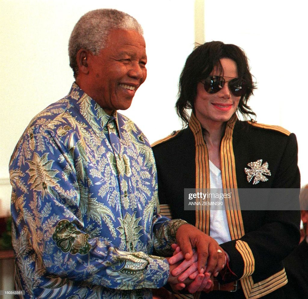 South African President Nelson Mandela (L) and US singer Michael Jackson clasp hands at a press conference at the President's home Genadendal in Cape Town 23 March 1999. Michael Jackson announced his latest project, 'Michael Jackson and Friends - The Adventure of Humanity' which will raise money to aid needy people around the world. The Nelson Mandela Children's Fund, UNESCO and the Red Cross are amongst the organisations which will benefit from the project which will include two concerts.