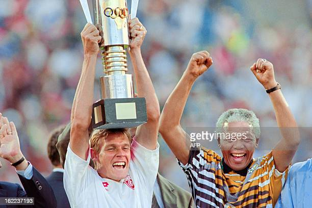 South African President Nelson Mandela celebrates with the national squad captain Neil Tovey holding the trophy on February 03 1996 after South...