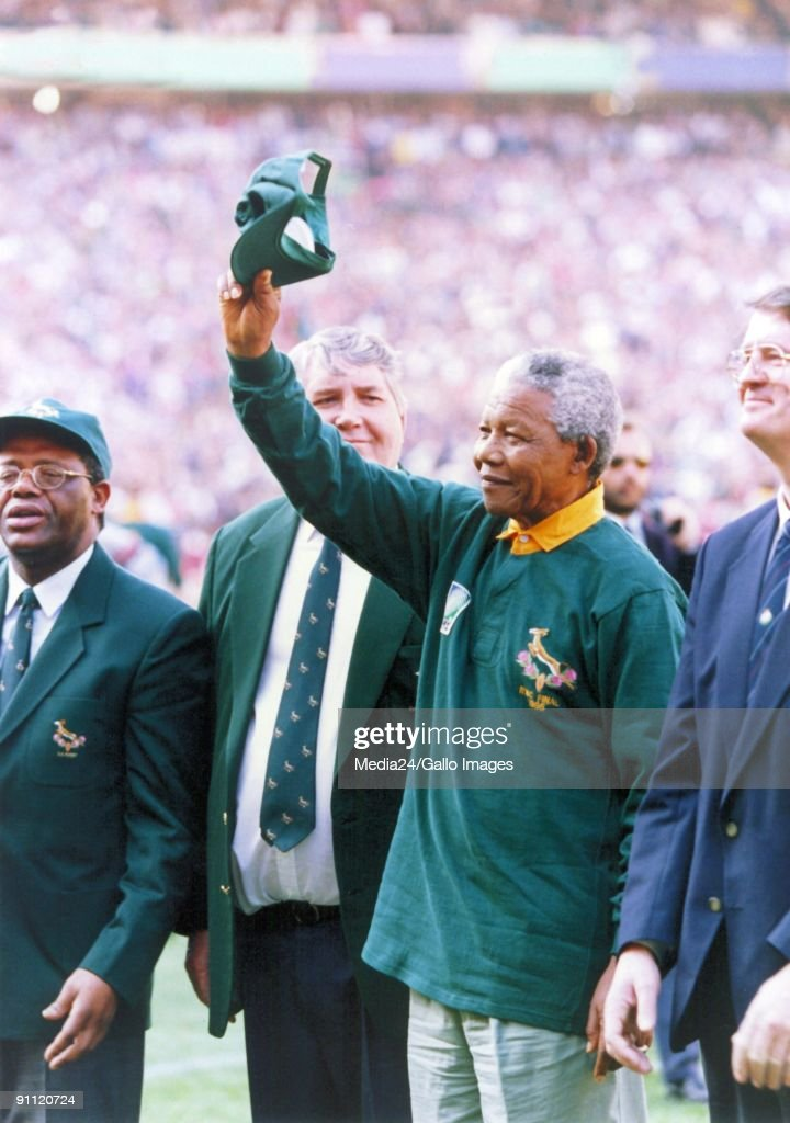 South African president Nelson Mandela, dressed in a No 6 Springbok jersey, celebrates after South Africa beat the All Blacks by 15-12 to win the 1995 Rugby World Cup. : News Photo