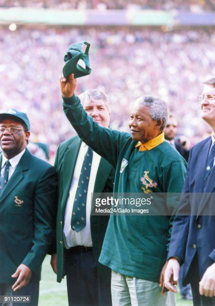 South African president Nelson Mandela dressed in a No 6 Springbok jersey celebrates after South Africa beat the All Blacks by 1512 to win the 1995...
