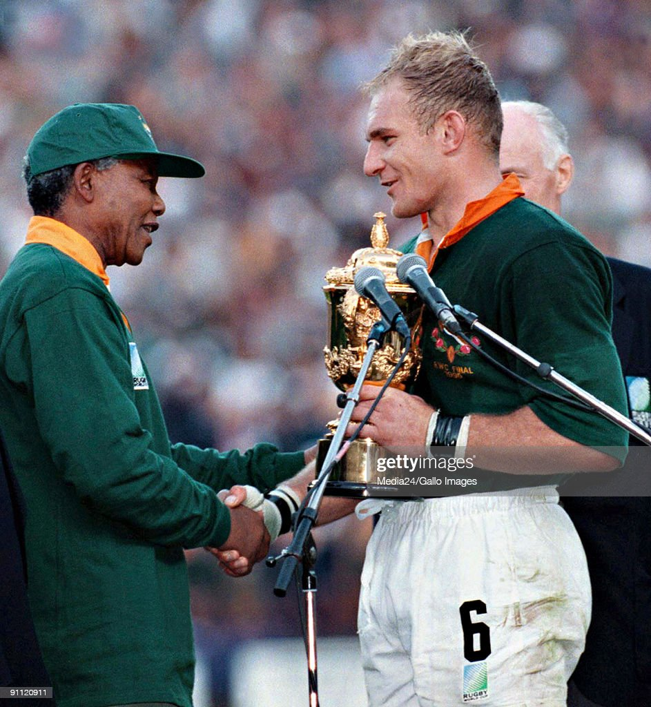 South African president Nelson Mandela, dressed in a No 6 Springbok jersey, congratulates the Springbok captain Francois Pienaar after South Africa beat the All Blacks by 15-12 to win the 1995 Rugby World Cup. : News Photo