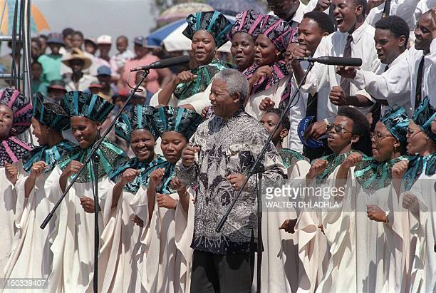 South African President Nelson Mandela joins the choral group at the signing of the country's new constitution at Sharpeville stadium on December 10...