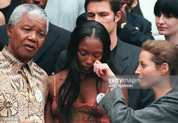 South African President Nelson Mandela poses with British supermodel Naomi Campbell as model Christy Turlington gestures at Genadendal his Cape Town...