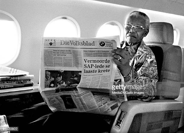 South African president Nelson Mandela relaxes on board the presidential jet with a copy of Die Volksblad an Afrikaans newspaper