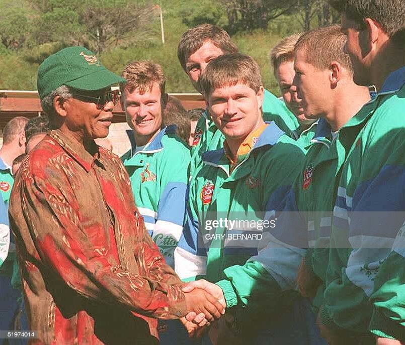 South African President Nelson Mandela(L) shakes hands with South African national rugby team member Tiaan Straus as his teammates look on 24 May in Capetown. The Springboks will play the defending world champion team of Australia for the opening game of the 1995 World Cup 25 May.