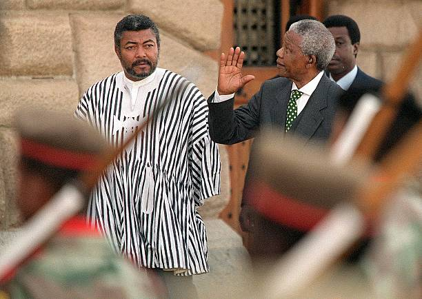 South African President Nelson Mandela waves to spectators as he and President of Ghana Jerry Rawlings inspects 09 July the guard of honour on...
