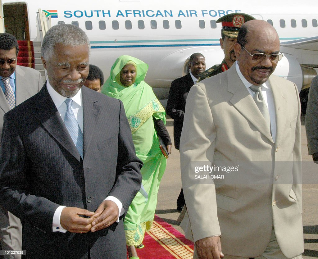 South African President Thabo Mbeki is greeted by Sudanese President Omar Al-Bashir in Khartoum 30 December 2004. Mbeki is in Sudan for talks on the Darfur conflict.