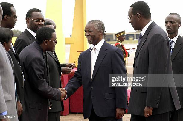 South African President Thabo Mbeki shakes hands with an unidentified person upon his arrival at Kigali International Airport 13 February 2004 to...
