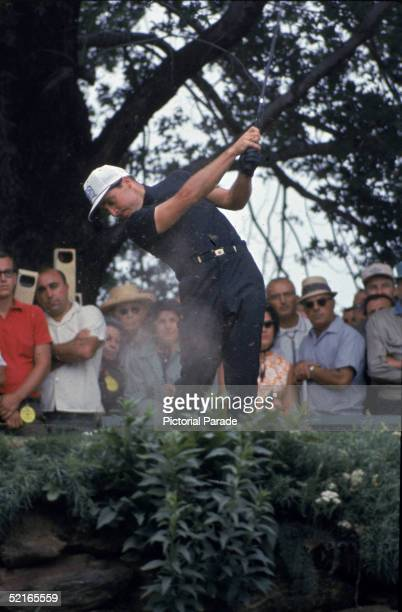 South African professional golfer Gary Player swings a club and hits the ball on the fourteenth hole in front of spectators at the US Open golf...