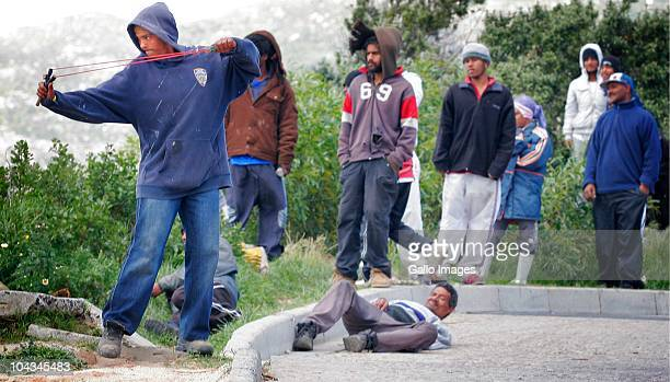 A South African protestor uses a catapult to attack police Violence broke out in Hout Bay near Cape Town South Africa on 21 September 2010 when...