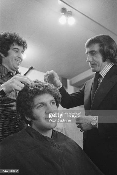 South African racing driver Jody Scheckter has his hair styled as fellow driver Jackie Stewart looks on 26th February 1974