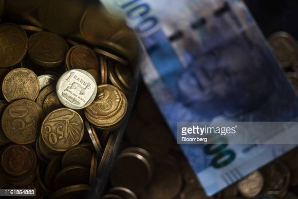 South African rand coins sit alongside a South African 100 rand banknote in this arranged photograph in Pretoria, South Africa, on Wednesday, Aug....
