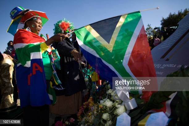 South African residents draped in the country's flag mourn at a monument of the Soweto Uprising at Hector Pieterson Museum in Soweto on June 16 2010...