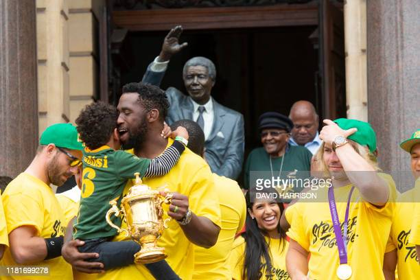 TOPSHOT South African Rugby captain Siya Kolisi holds the Web Ellis Trophy and his son during the South African Rugby World Cup winner team's last...