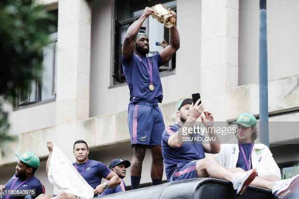South African Rugby captain Siya Kolisi holds up the Web Ellis trophy as the World Cup winner team parades at the promenade at the North Beach on an...