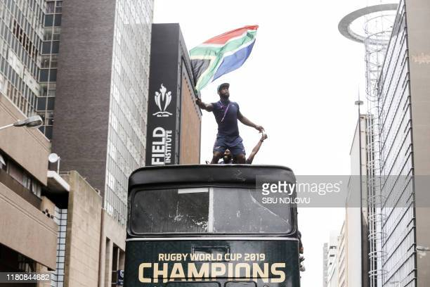 South African Rugby captain Siya Kolisi waves the South African flag as the World Cup winner team parades in the Durban CBD on an open top bus on...