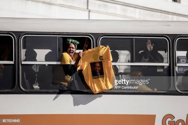 South African ruling party African National Congress and South African President Jacob Zuma supporters shout holding a tshirt as they drive in a bus...