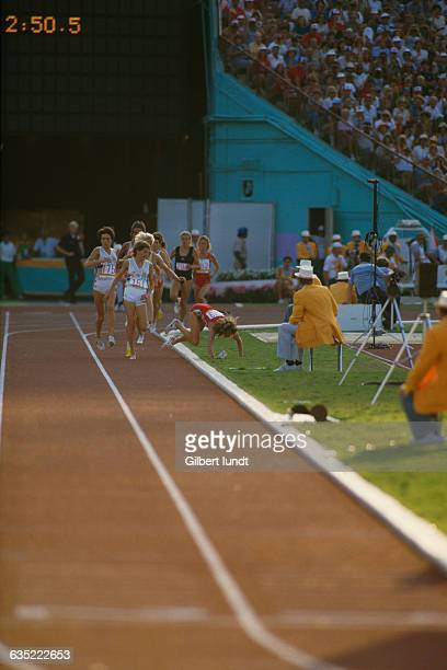 South African runner Zola Budd watches her chief competitor, American Mary Decker, fall to the ground in the final of the Women's 3,000-meter run at...