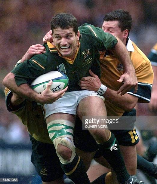 South African scrumhalf and captain Joost Van Der Westhuizen is tackled by Australian fullback Matthew Burke during the Rugby World Cup semifinal...
