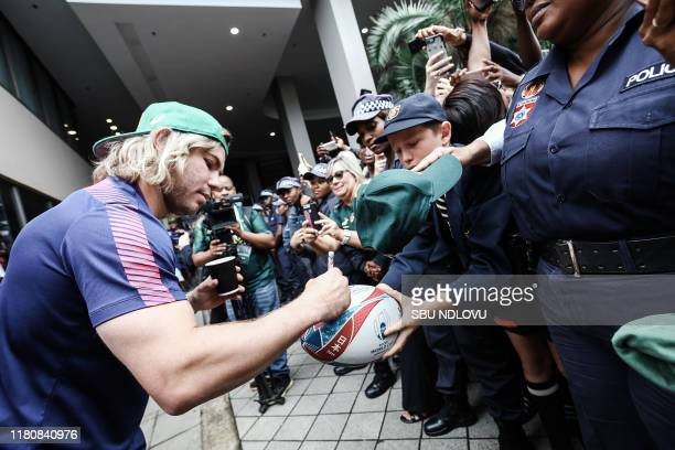 South African scrumhalf Faf de Klerk signs an autograph on a rugby ball for a supporter as the World Cup winner team parades in the Durban CBD on an...