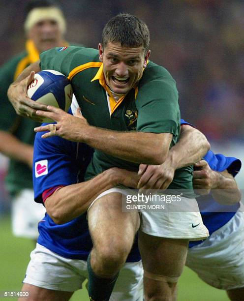 South African scrumhalf Joost Van Der Westhuizen is tackled by French players during the rugby test match between France and SouthAfrica 10 November...