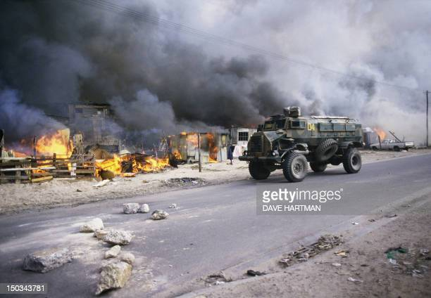A South African security forces armored vehicle patrols on June 9 1986 by hundreds of burning houses in the KTC squatter community camp of Cape Town...