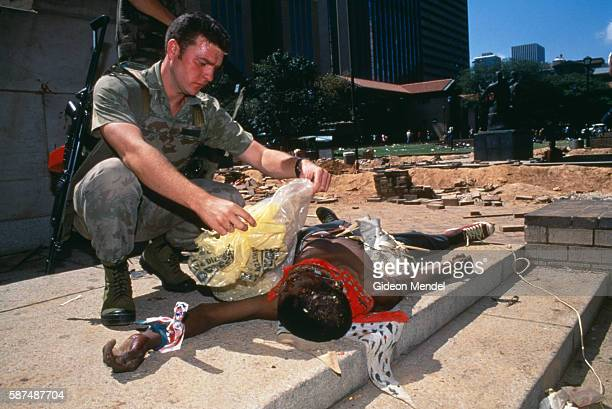 A South African soldier covers the body of a man killed in a clash between the African National Congress and the Inkatha Freedom Party in Johannesburg