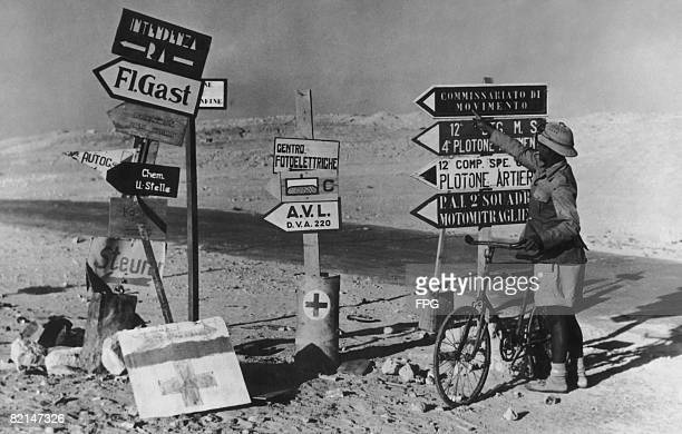 A South African soldier points at an Italian road sign in Libya during World War II circa 1941 He has been released from a recent offensive and is...