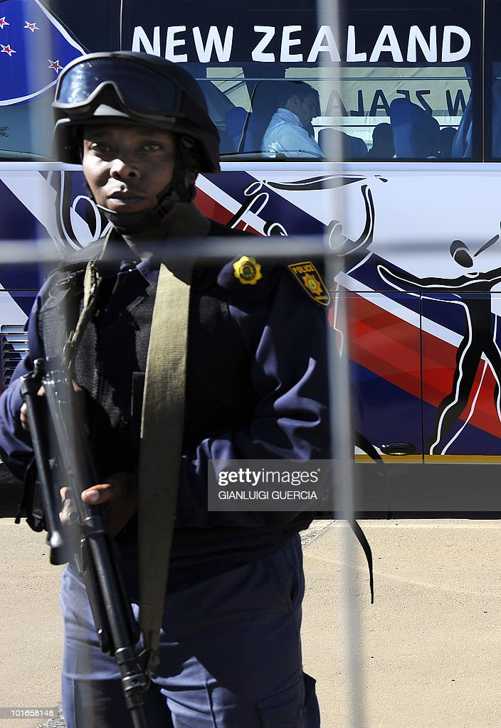 A South African special protection unit policeman stands guard at the O.R. Tambo international airport in Johannesburg as a bus carrying part of New Zealand's national football team leaves from a terminal on June 6, 2010 ahead of the 2010 World Cup football tournament.