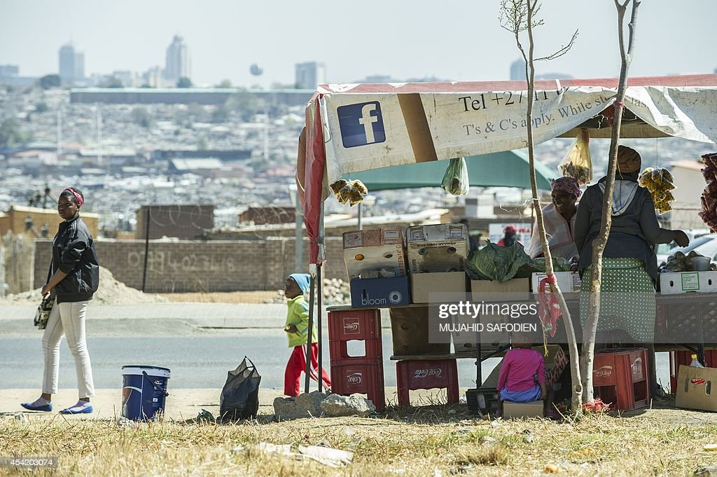 A South African street vendor trades with customers in Alexandra Township on the backdrop of the Sandton Towers, one of Africa's leading and most prestigious shopping centres, on August 26, 2014 in...