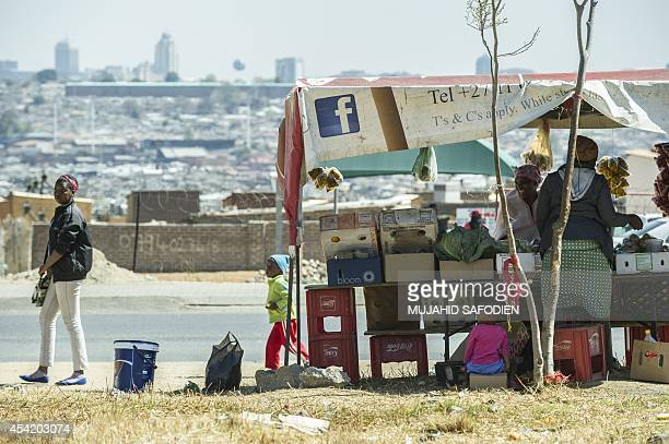 A South African street vendor trades with customers in Alexandra Township on the backdrop of the Sandton Towers one of Africa's leading and most...