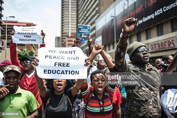 South African students hold placard gesture and chant slogans while they take part in a protest march towards the Union Buildings during a...