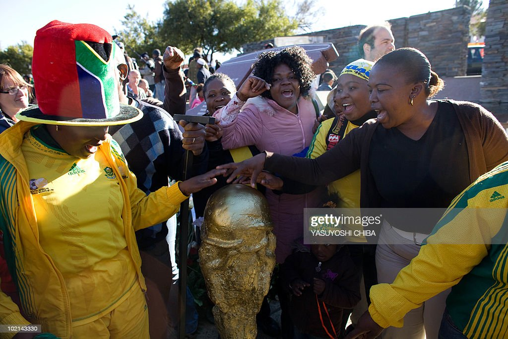 South African supporters cheer near a mock trophy made by a local artist near the Hector Pieterson Museum in Soweto on June 16, 2010. South Africa paused from its World Cup celebrations today to observe the 34th anniversary of the Soweto uprising, a student protest whose tragic ending galvanised the anti-apartheid movement. On June 16, 1976, thousands of students from the black township of Soweto gathered to march in protest at being forced to go to school in Afrikaans, the language of the white-minority regime. Police opened fire on the unarmed protestors, killing hundreds -- including Hector Pieterson, the first to die in the violence.