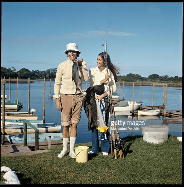 South African surgeon Christiaan Barnard showing a freshly caught fish under the pleased gaze of his wife Barbara Zoellner Plettenberg Bay 1977