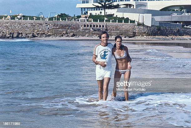 South African surgeon Christiaan Barnard walking hugging his wife Barbara Zoellner by the sea Plettenberg Bay 1977