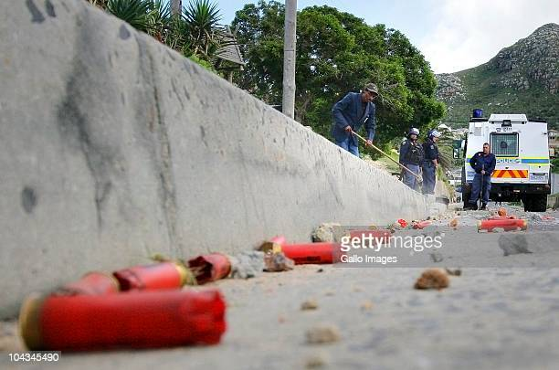 South African sweepers clean the road of rubber bullets after violence broke out in Hout Bay near Cape Town South Africa on 21 September 2010 when...