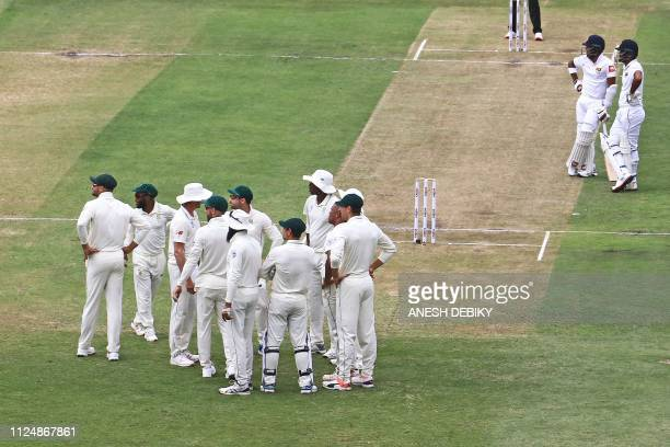 South African team players and Sri Lankan Drimuth Karunaratne and Oshada Fernado look at the big screen for the review decision during day 2 of the...