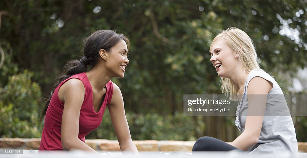South African teen culture - Two young woman sitting on a trampoline. :  Stock Photo