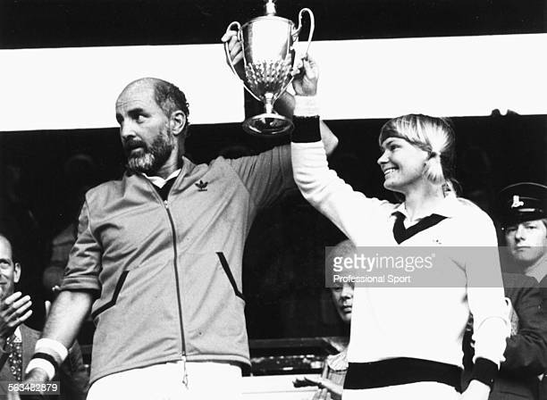 South African tennis players Bob Hewitt and Greer Stevens smile as they hold up the trophy in the royal box after winning the mixed doubles...