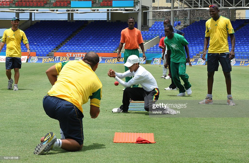 South African trainer Robert Walter (L) batsman Ashwell Prince (2nd L) and bowler Lonwabo Tsotsobe (R) during a training clinic for members of the St. Kitts Junior Cricket Academy team, before the second test at the Warner Park ground in the St Kitts capital of Basseterre on June 16, 2010. South Africa have taken a 1-0 lead in the three-Test series, with the second test beginning on June 18. AFP PHOTO/Mark RALSTON